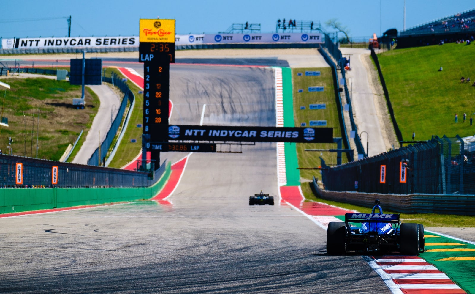 Two cars speed down COTA main straight during IndyCar practice